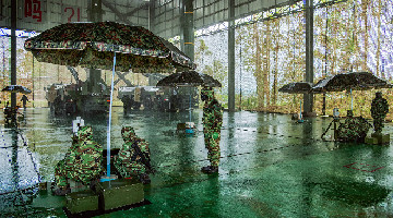 Soldiers operate short-range ballistic missile systems in heavy rain