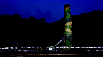 PLA Rocket Force soldiers erect DF-21 missiles at night