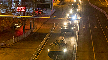 Armored vehicles move through urban area at night
