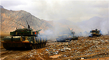 Armored vehicles maneuver at simulated battlefield