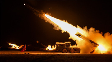 Female soldiers fire rockets at night in desert