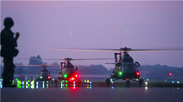 Transport helicopters ready to lift off at night