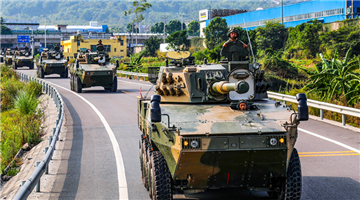 Armored assault vehicles drive on highway