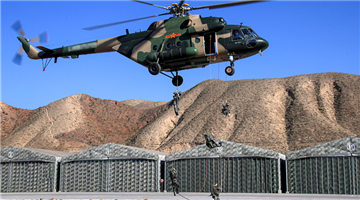 Soldiers fast-rope from hovering helicopters
