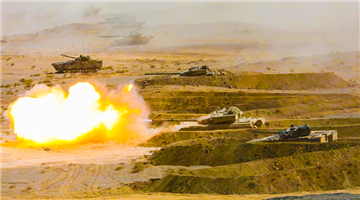 Armored vehicles engage mock enemy targets