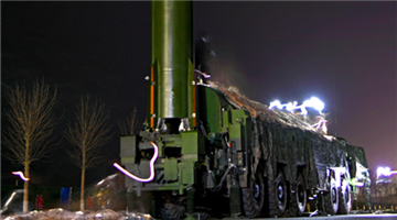 Soldiers erect ballistic missile system at night