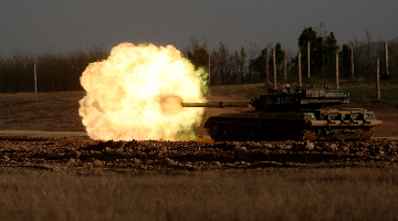 Tanks attack mock targets during live-fire training